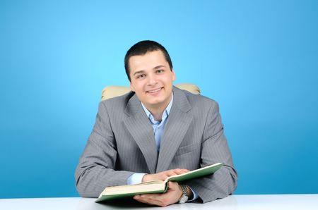 Handsome businessman holding book on blue background Stock Photo - 6338000