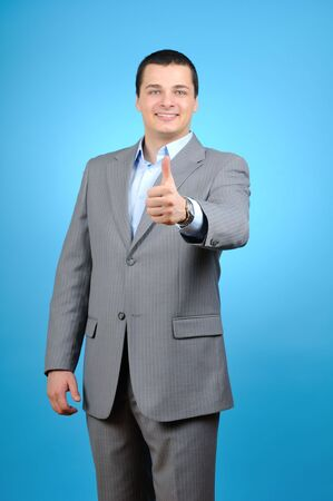 Handsome businessman thumb up on blue background  photo