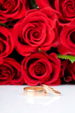 Red roses and two golden wedding rings photo