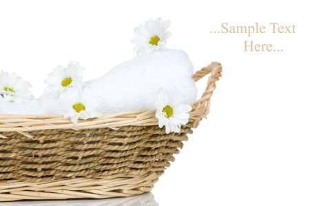 Towel and Chamomile flowers in a basket isolated on white background  photo