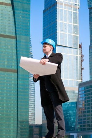 Engineer with blue hard hat holding drawing on skyscrapers background photo