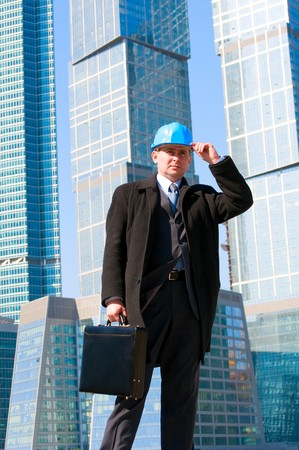 Engineer with blue hard hat holding briefcase on skyscrapers background photo