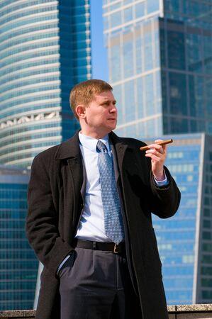Businessman with cigar near skyscrapers photo