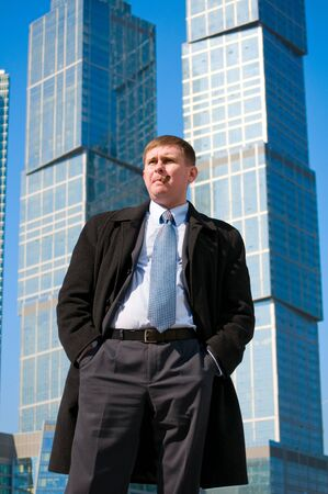 Businessman with cigar near skyscrapers photo