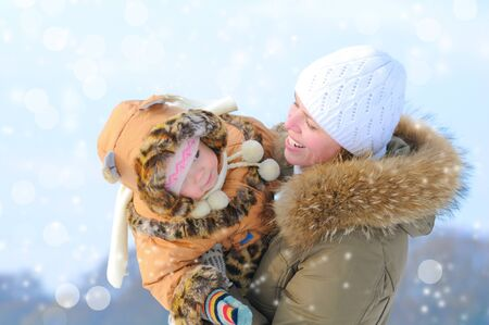 Happy young mother and daughter in winter clothing  have fun