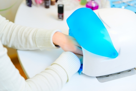 Manicure in process Uv lamp for nails photo