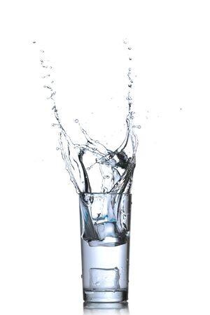 welling: Vetro di acqua con cubetti di ghiaccio su sfondo bianco Archivio Fotografico