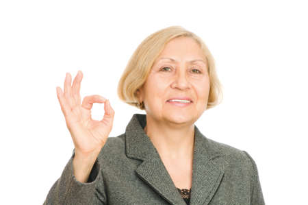 Portrait of a smiling senior business woman showing okay symbol isolated on white background photo