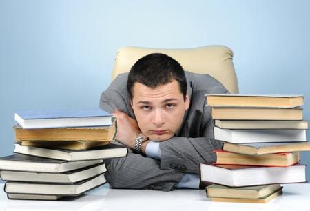 Tired businessman in the books on blue background Stock Photo - 18523604
