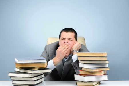 Tired businessman in the books on blue background photo
