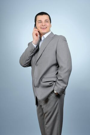 Handsome businessman talking with cell phone on blue background  photo