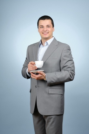 Handsome businessman holding cup of tea on blue background photo