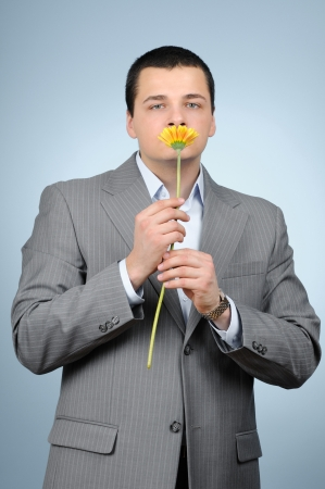 Handsome businessman holding gerber flower on blue background  photo