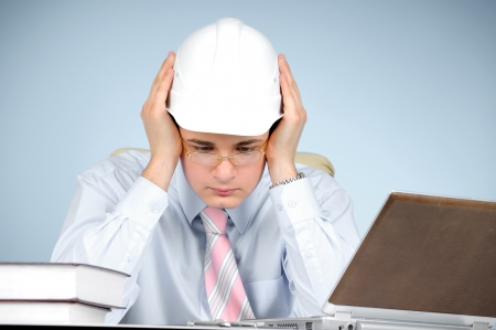 An engineer with white hard hat at work on blue background  photo
