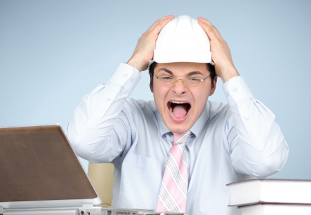 Crazy engineer with white hard hat at work on blue background  photo
