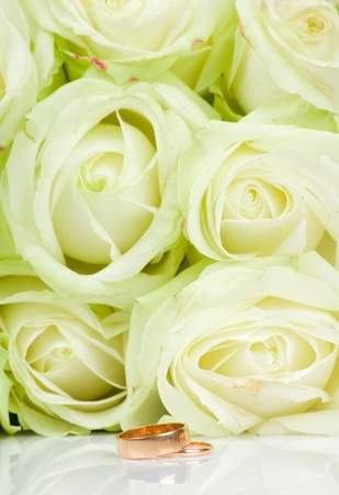 White roses and two golden wedding rings photo