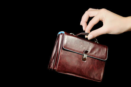 Leather Briefcase In Female Hand Isolated On Black Background  Concept photo