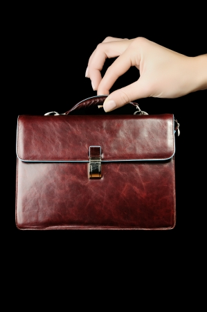 woman handle success: Leather Briefcase In Female Hand Isolated On Black Background  Concept