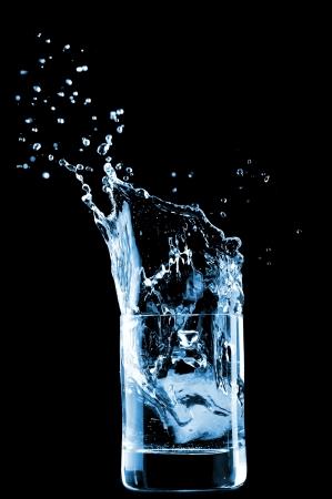 purified: El agua en el vidrio aislado sobre fondo negro