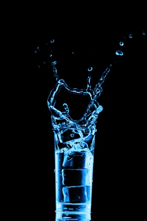 welling: Glass of water with ice cubes on black background