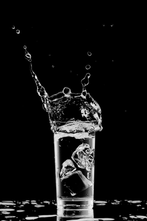 soda splash: Water in the glass on black background