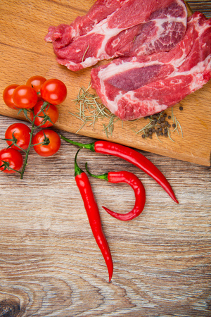 Fresh steaks with vegetables on the wooden table photo