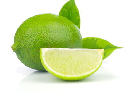 Limes whole and slices with green leaves  Isolated on white background Stock Photo