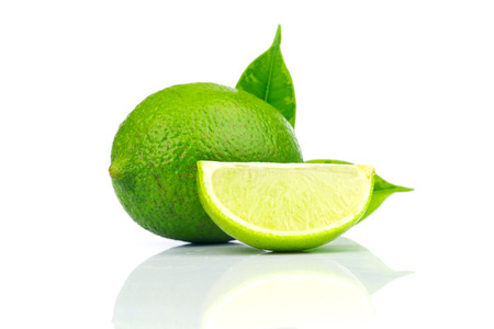 Limes whole and slices with green leaves  Isolated on white background photo