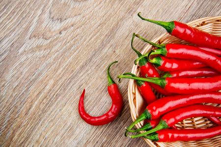 Organic chili peppers on wooden background photo