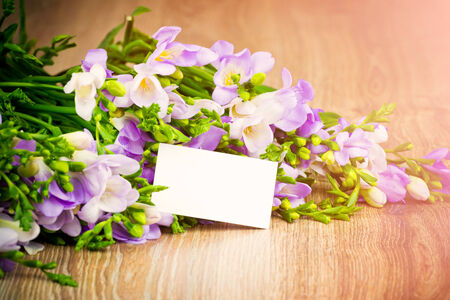 Lilac freesia on wooden table photo