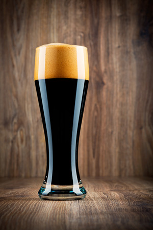 Glass of beer on wooden background photo