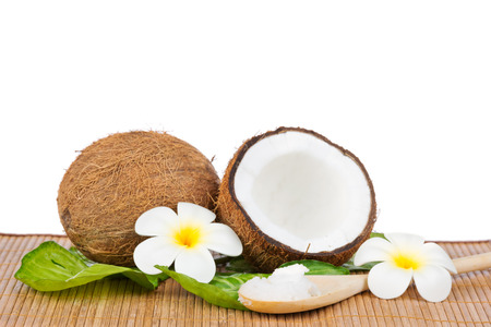Coconut with green leaf and coconut oil on the wooden spoon Standard-Bild