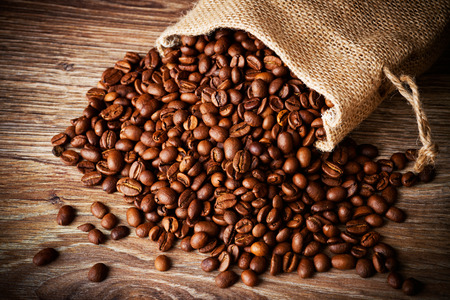The sack of coffee beans on wooden background photo