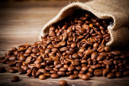 molinillo: El saco de granos de café en el fondo de madera