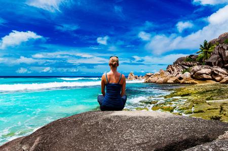 meditates: Young woman meditates on the beach Stock Photo