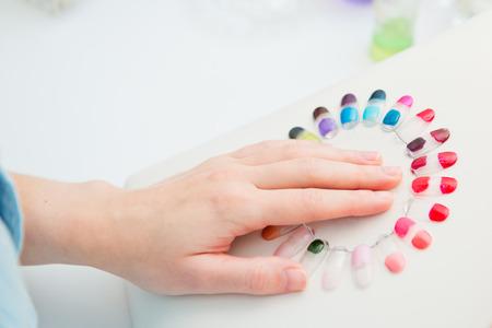 selects: Manicure nel processo di donna sceglie un colore di smalto