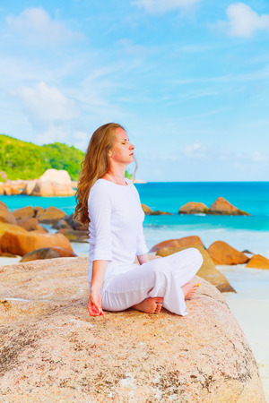 Young woman meditates on the beach photo