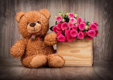 Rosas en la caja y un oso de peluche en el fondo de madera