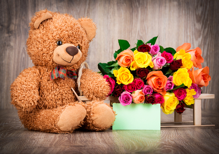 teddy bear background: Roses and a teddy bear on wooden background