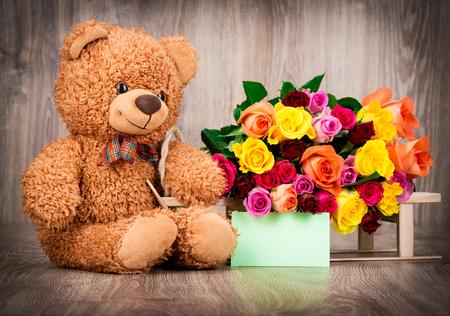 teddy bear love: Roses and a teddy bear on wooden background