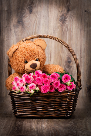 teddy bear background: Roses and a teddy bear in the wicker on wooden background Stock Photo
