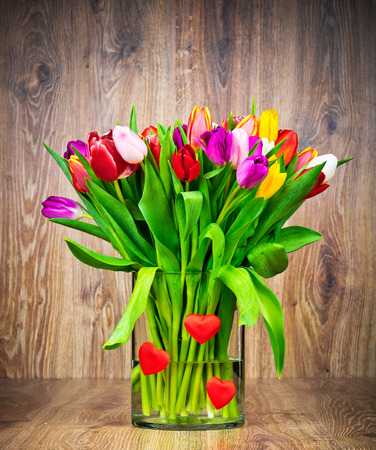 Tulips in the vase on wooden background photo