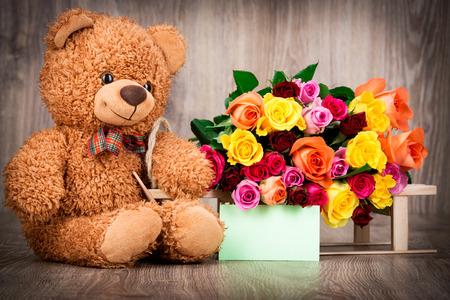 oso de peluche: Rosas y un osito de peluche en el fondo de madera