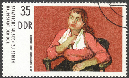 ddr: MOSCOW, RUSSIA - CIRCA FEBRUARY, 2016: a stamp printed in DDR shows a painting A girl in red by Rudolf Bergander, the series Berlin. Municipal gallery, circa 1974