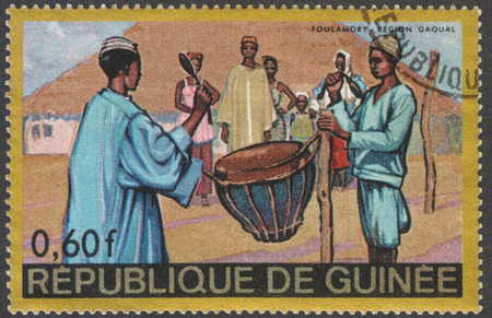 postmail: MOSCOW, RUSSIA - CIRCA FEBRUARY, 2016: a stamp printed in GUINEA shows a scene of traditional native life, the series Regional Costumes and Habitations, circa 1967 Editorial