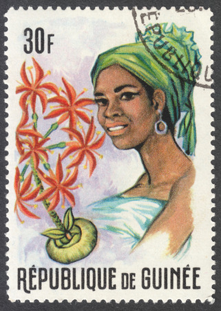 headdresses: MOSCOW, RUSSIA - CIRCA JANUARY, 2016: a stamp printed in GUINEA shows a woman in the traditional headdress and a plant Haemanthus sp., the series Guinean Flora and Female Headdresses, circa 1966