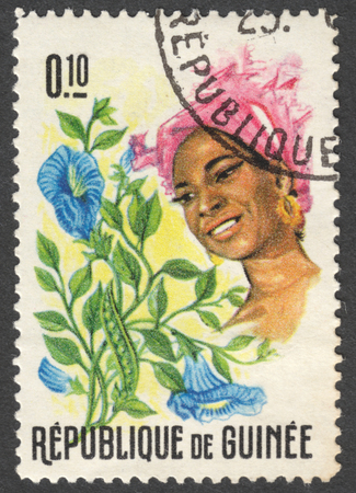 sello: MOSCOW, RUSSIA - CIRCA JANUARY, 2016: a stamp printed in GUINEA shows a woman in the traditional headdress and a plant Clitoria sp., the series Guinean Flora and Female Headdresses, circa 1966