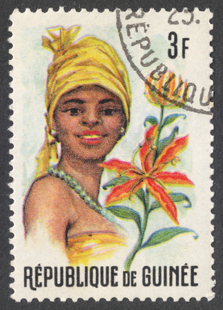 headdresses: MOSCOW, RUSSIA - CIRCA JANUARY, 2016: a stamp printed in GUINEA shows a woman in the traditional headdress and a plant Gloriosa sp., the series Guinean Flora and Female Headdresses, circa 1966 Editorial