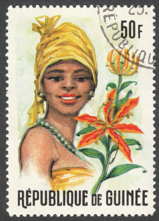 MOSCOW, RUSSIA - CIRCA JANUARY, 2016: a stamp printed in GUINEA shows a woman in the traditional headdress and a plant Gloriosa sp., the series Guinean Flora and Female Headdresses, circa 1966 Editorial