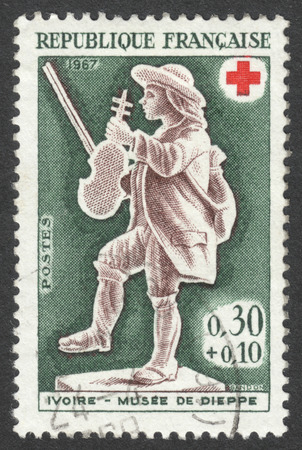 postes: MOSCOW, RUSSIA - CIRCA APRIL, 2016: a post stamp printed in FRANCE shows a fiddler, the series Red cross, circa 1967